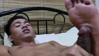 Cute Asian twink sniffs his shoes before jerking on a bed